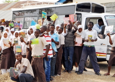 Students from Buyani High School posing with the TRLF bus which transports the books to the school